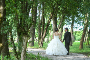 A rear view of the bride and groom holding hands, looking at each other and walking down a pathway in the forest.